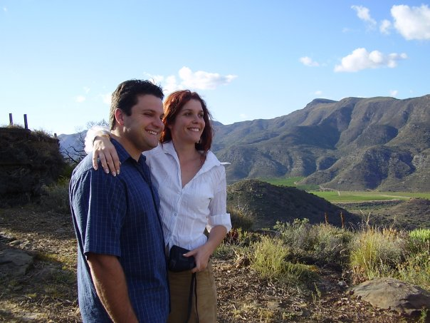 A smiling young man and woman standing on a hill overlooking a valley