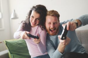 Happy couple playing video games on console and having fun