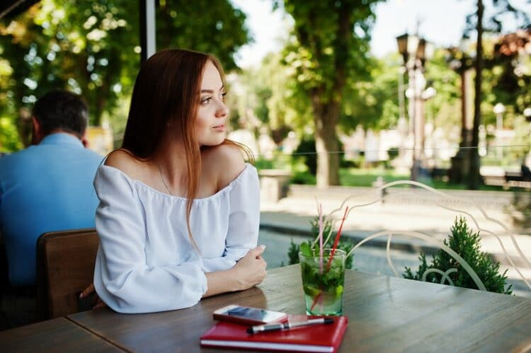 Portrait of a beautiful businesswoman sitting at a table with red notebook, pen, smartphone and a drink on it.