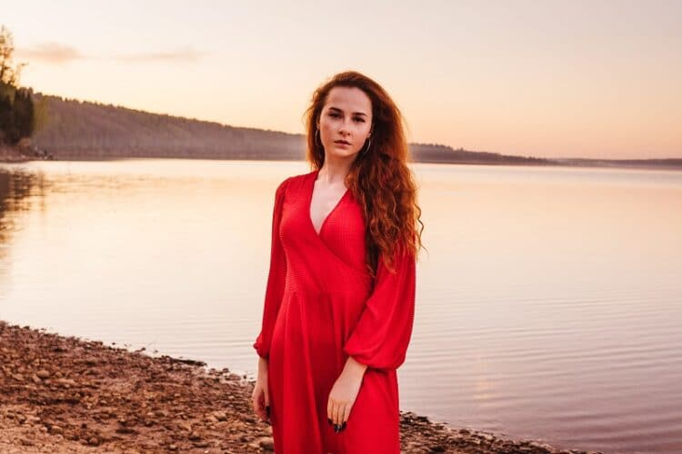 Young ginger woman in red dress at sunset. Back light in hair. River or lake on background, pink sky